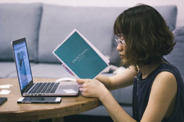 Imagen de una chica leyendo junto a su ordenador