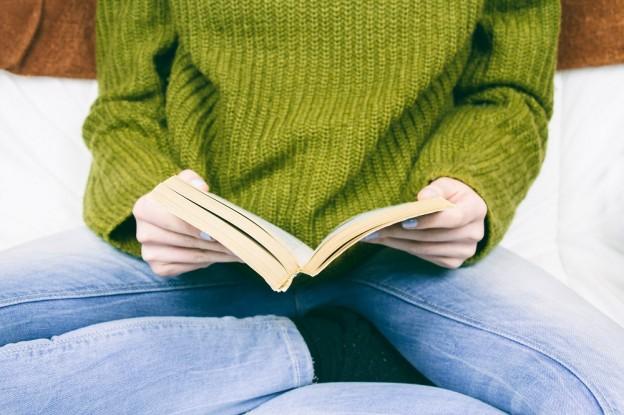 Persona con jersey verde y vaqueros leyendo un libro